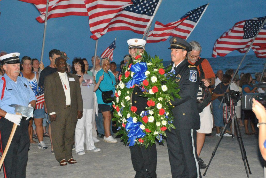 Uniformed Officers Holding a Patriotic Wreath on the Beach with Onlookers